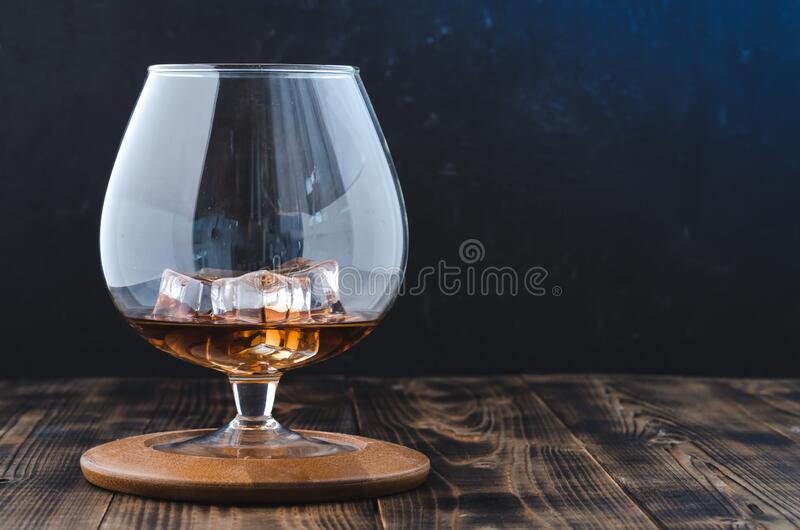 Glass of cognac with ice cubes on a wooden bar/Glass of cognac with ice cubes on a wooden bar. Blue light background with royalty free stock photography