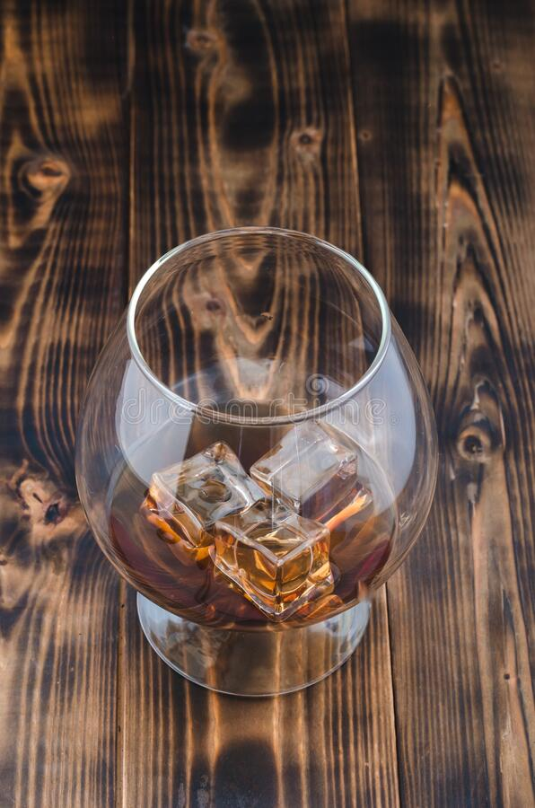 Glass of cognac with ice cubes on a wooden table/Glass of cognac with ice cubes on a wooden bar. Beautiful glass royalty free stock image