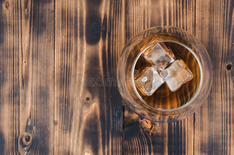Glass of cognac with ice cubes on a wooden table/Glass of cognac with ice cubes on a wooden bar. Top view, copyspace royalty free stock images
