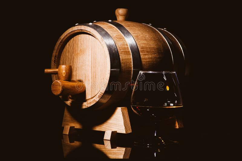 Glass of cognac with oak barrel on black background. Wooden barrel for whiskey with glass. Aged alcohol beverage bourbon brandy distillery drink liquid old rye royalty free stock photo