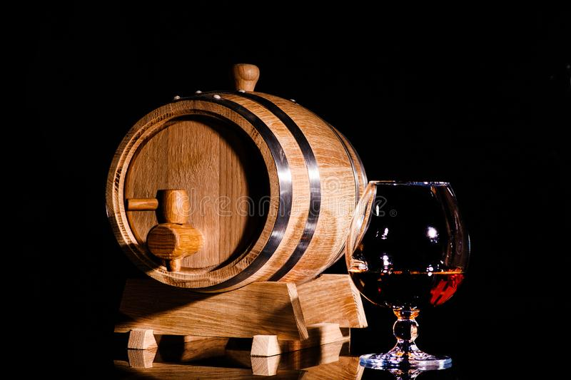 Glass of cognac with oak barrel on black background. Wooden barrel for whiskey. With glass stock photo