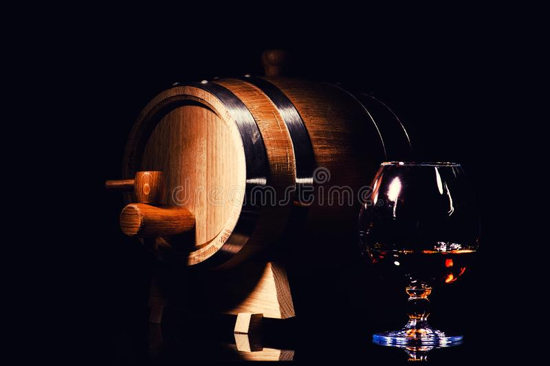 Glass of cognac with oak barrel on black background. Wooden barrel for whiskey with glass. Aged alcohol beverage bourbon brandy distillery drink liquid old rye royalty free stock photography