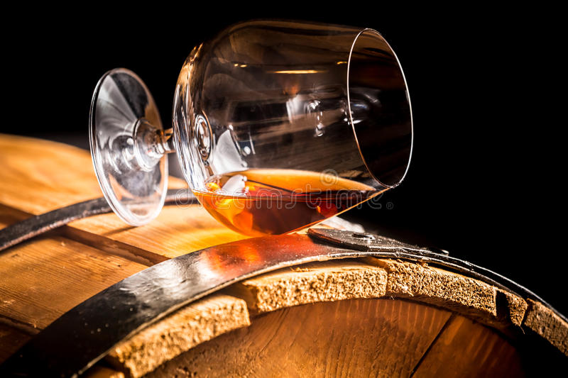 Glass of cognac on the old wooden barrel stock photography