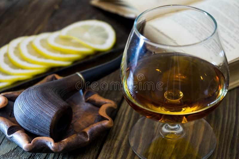 A glass of cognac, a pipe in the ashtray, sliced lemon on a glass plate and an old book on textured oak table. stock photos