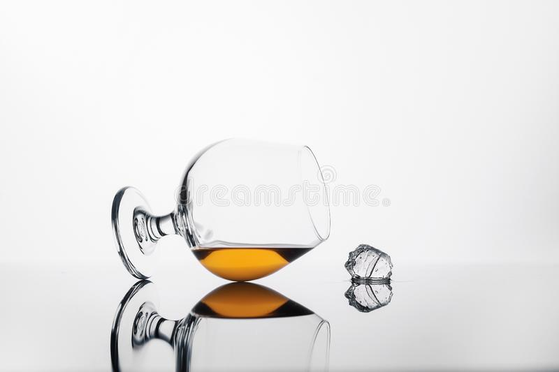 Glass with cognac or whiskey on a white background and a cube of ice stock image
