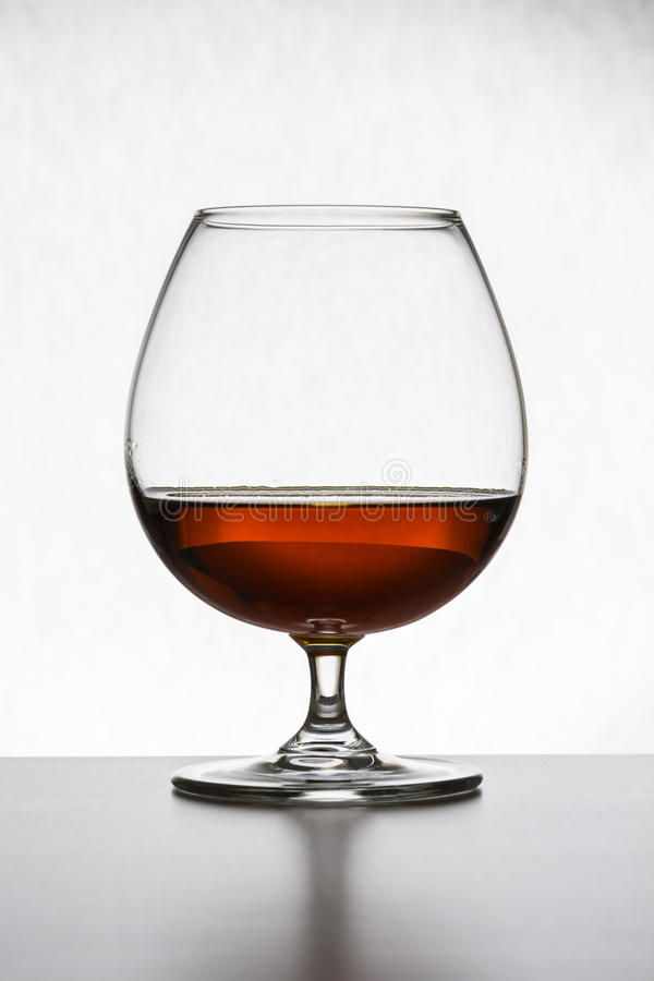 Glass with cognac on white background . Front view. Close up shot. High resolution stock images