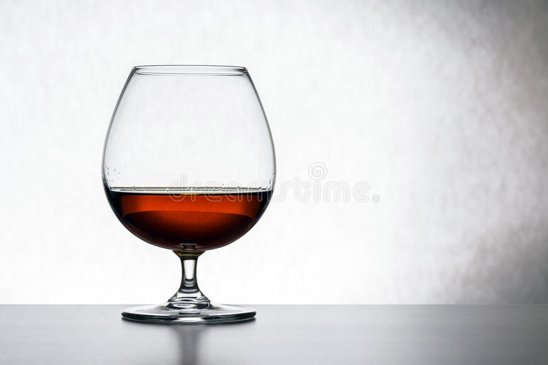 Glass with cognac on white background isolated. Front view. Close up shot. High resolution stock photo