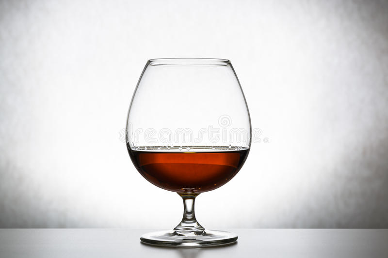Glass with cognac on white background isolated. Front view. Close up shot. High resolution royalty free stock photos