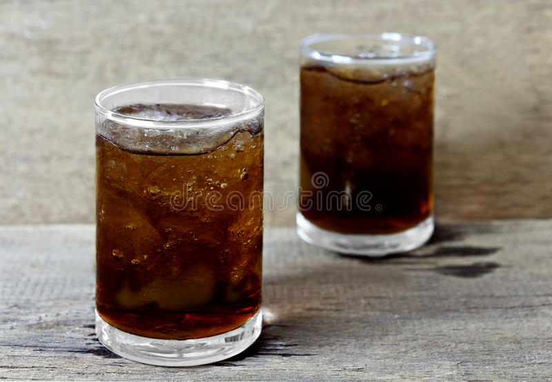 Glass of cola with ice on wooden table royalty free stock image