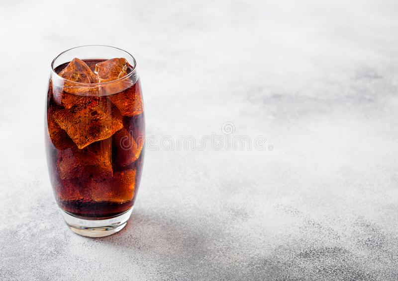 Glass of cola soda drink with ice cubes and bubbles on stone kitchen table background. stock photo