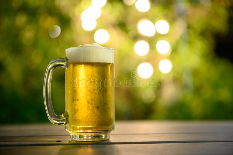 A glass of cold beer with a foam on top Placed on a table in the garden royalty free stock image