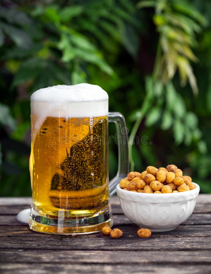 Glass of cold beer with snack, coated peanuts on wooden table in garden royalty free stock image