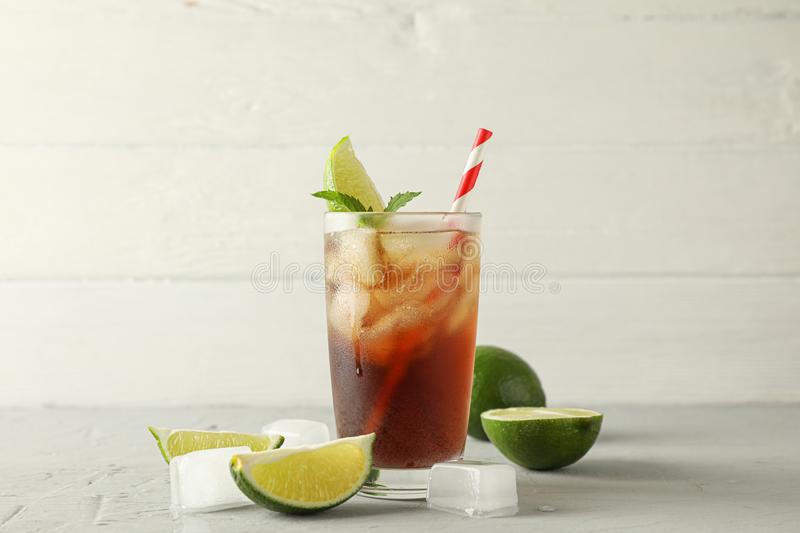 Glass with cold cola and citrus on grey cement background. Space for text stock photos
