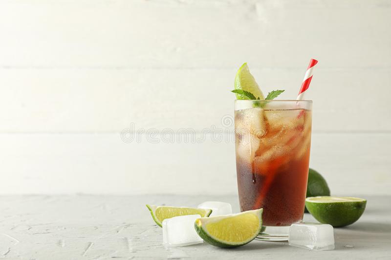 Glass with cold cola and citrus on grey cement background. Space for text royalty free stock photos