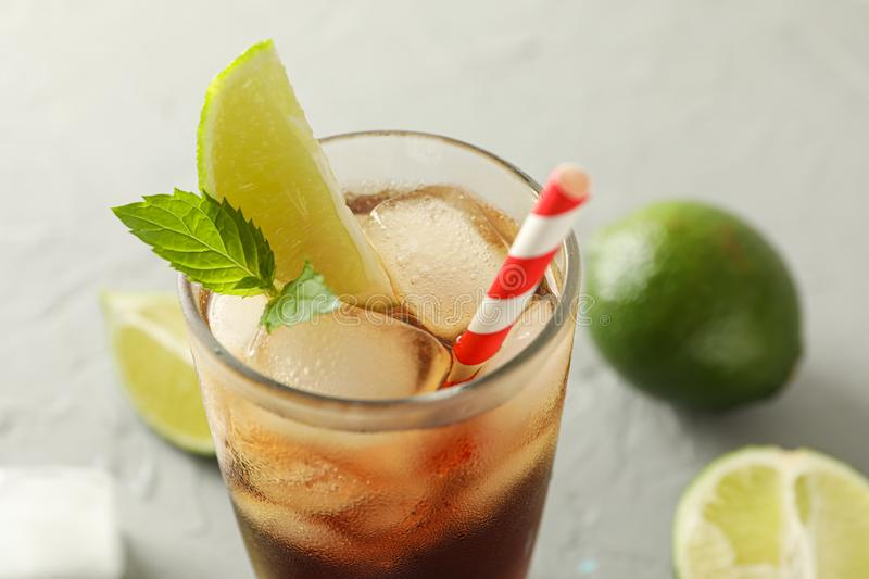 Glass with cold cola and citrus on grey cement background. Space for text royalty free stock photo