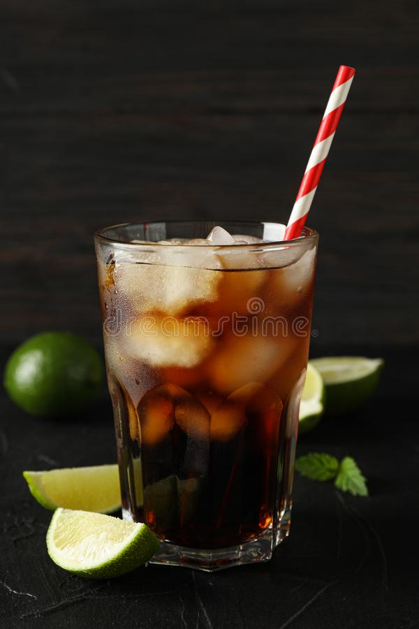 Glass of cold cola and limes on black background. Glass of cold cola and limes on black cement background stock photography