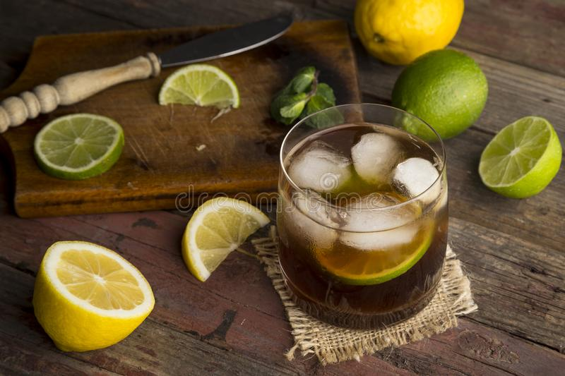 Glass of cold Cuba Libre Cocktail. High angle view of a glass of Cuba Libre cocktail with rum, coke, lemon juice and ice cubes on a rustic wooden table. Focus on stock photo