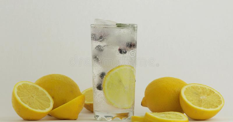 Glass with cold drink. Lemon, ice cubes and black currant in a drink glass royalty free stock photography