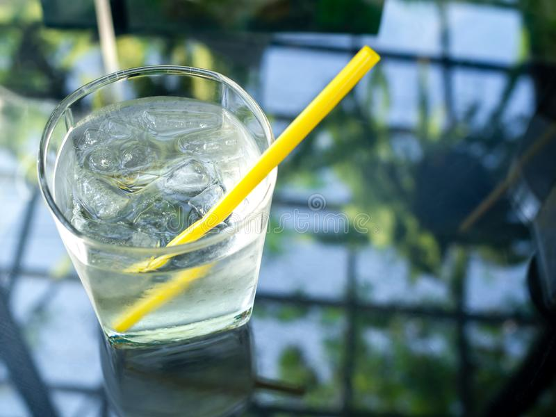 A glass of cold drinking water with yellow straw. A glass of cold drinking water with ice and yellow straw on glass table with copy space on top view royalty free stock photography