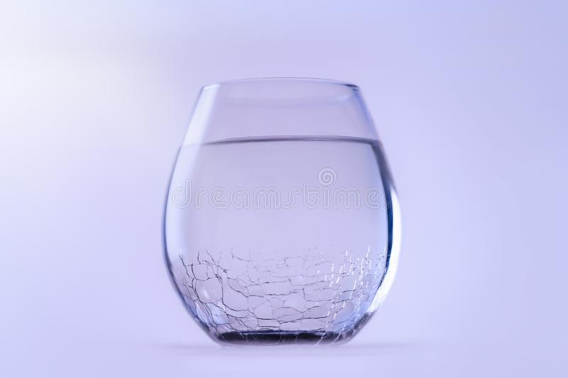 A glass of cold fresh water. A glass with a cracked glass, copy space. stock image