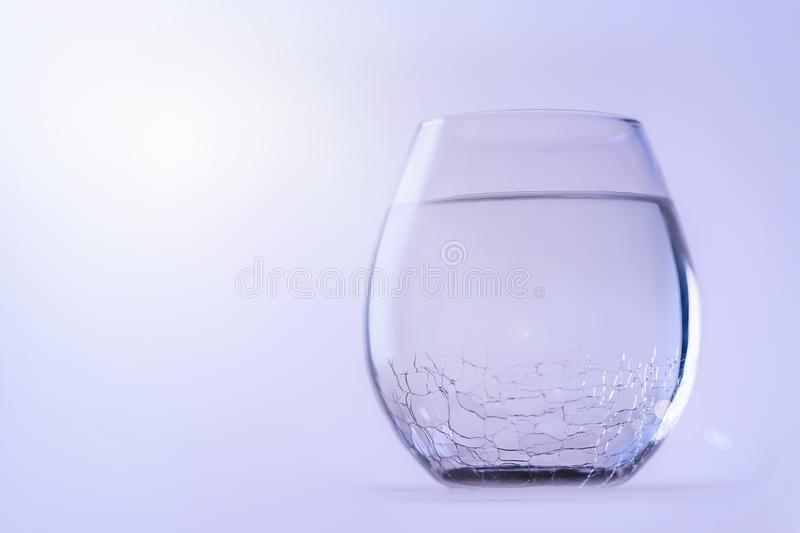 A glass of cold fresh water. A glass with a cracked glass, copy space. stock photos