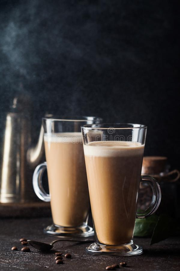 Glass with cold latte. Two glasses with cold coffee latte macchiato on table against black background royalty free stock images