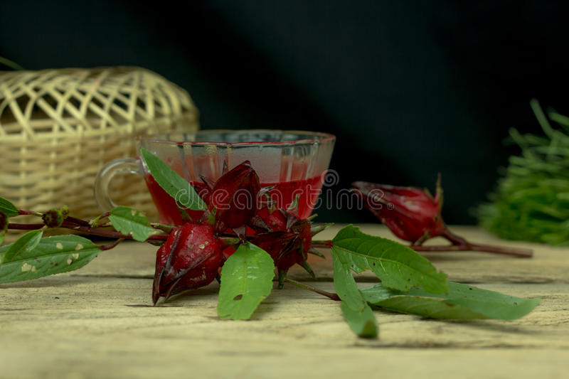 Glass of cold roselle juice - healthy food against wood. stock photo