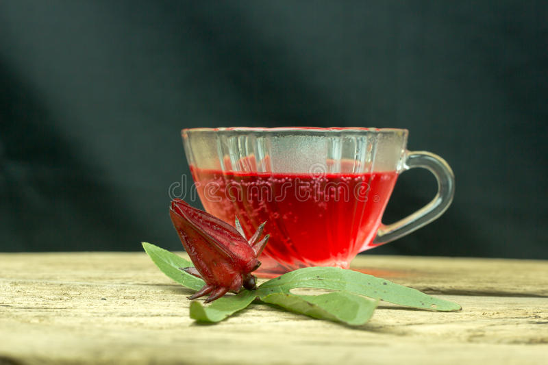 Glass of cold roselle juice - healthy food against wood. stock image
