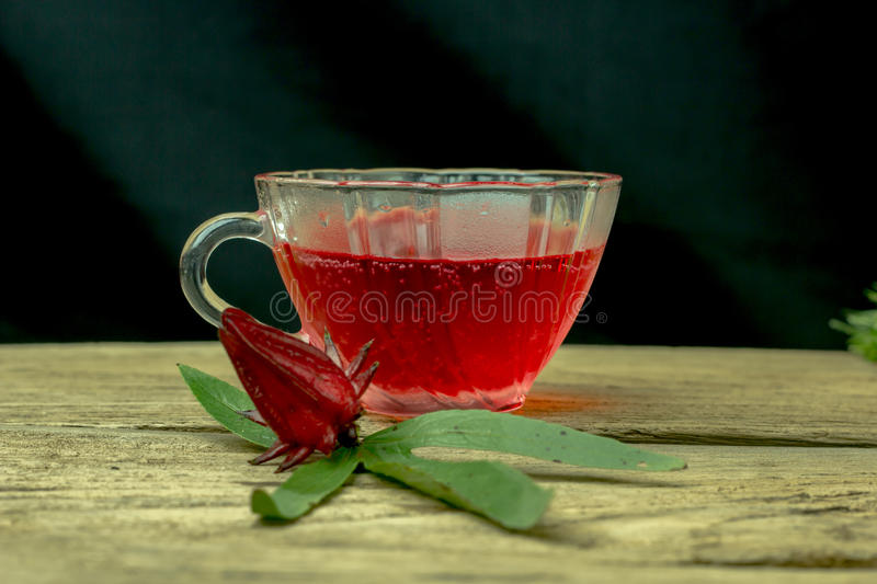 Glass of cold roselle juice - healthy food against wood. royalty free stock image