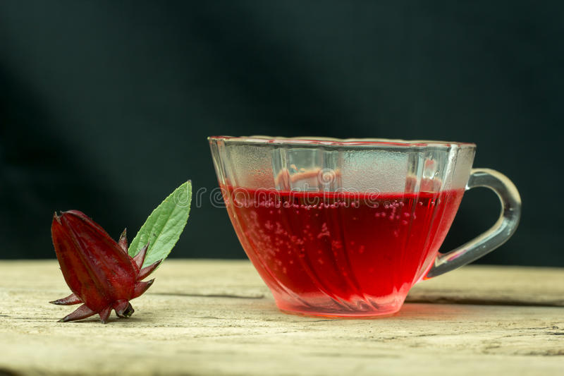 Glass of cold roselle juice - healthy food against wood. stock images