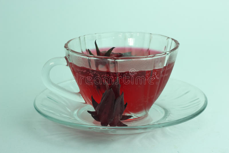 Glass of cold roselle juice - healthy food against wood. royalty free stock images