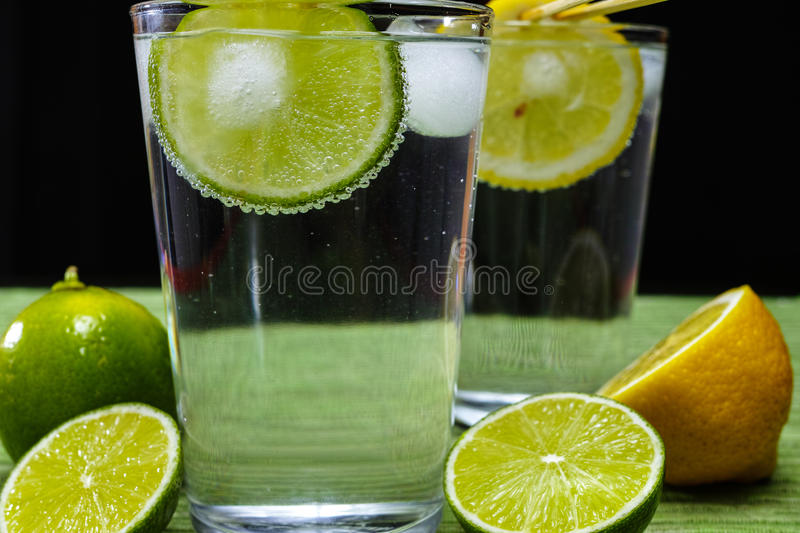 Glass with cold sparkling mineral water, lime and lemon. Seltzer royalty free stock photography