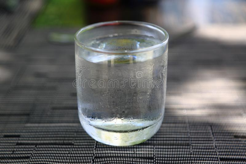 Glass of cold water on grey brown background on a warm summer day. Temperature contrast. Drinks background.n royalty free stock photography