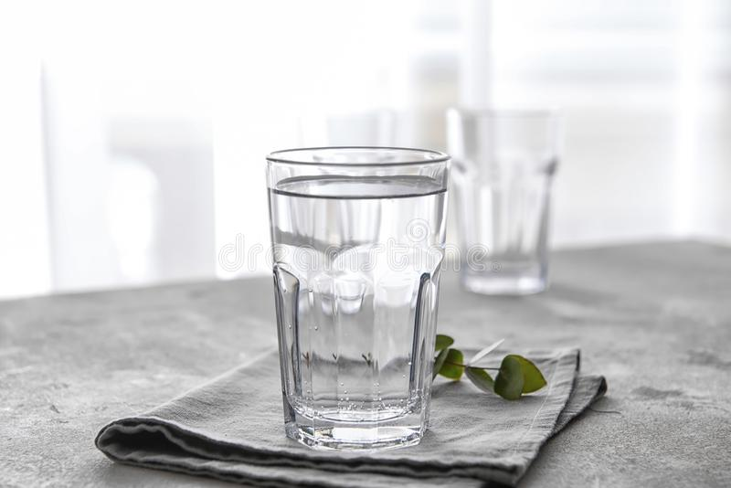 Glass of cold water on grey table stock photography