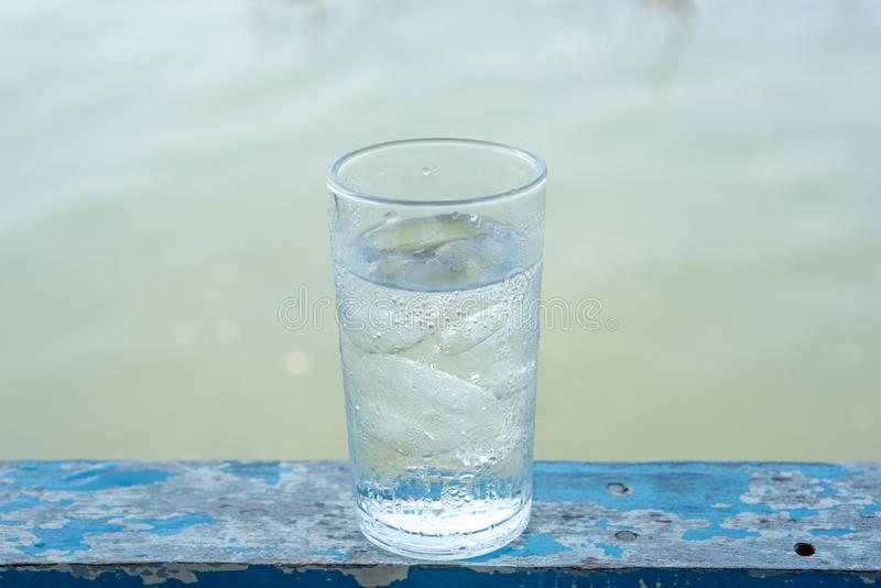 Glass cold water with ice. On sea background royalty free stock images