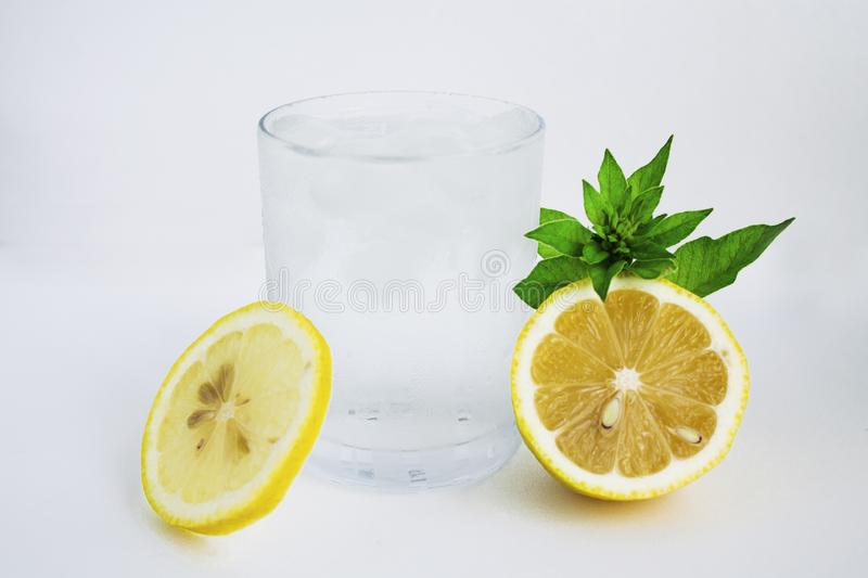 Glass with cold water, lemon and mint. Cool water on a white background stock photo