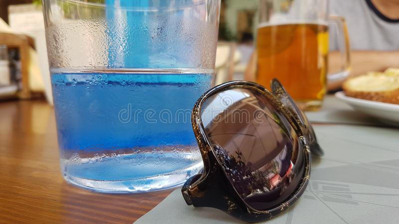 A glass of cold water and sunglasses stock image