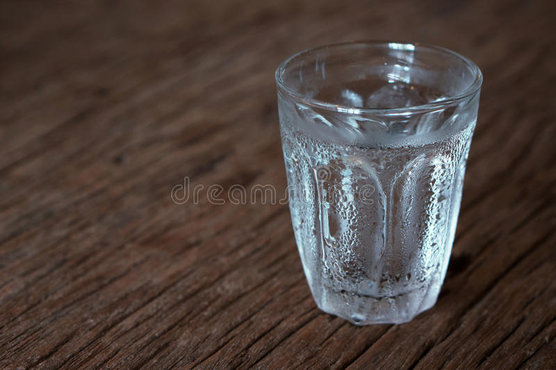 Glass of cold water. On wood table royalty free stock image
