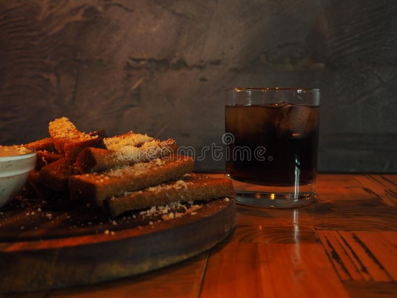 Glass of cold whiskey with ice on a wooden table in the dark bar stock photography