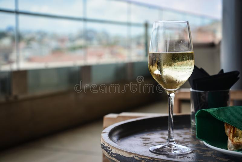 Glass with cold white wine on wooden table. At restaurant interior closeup stock image
