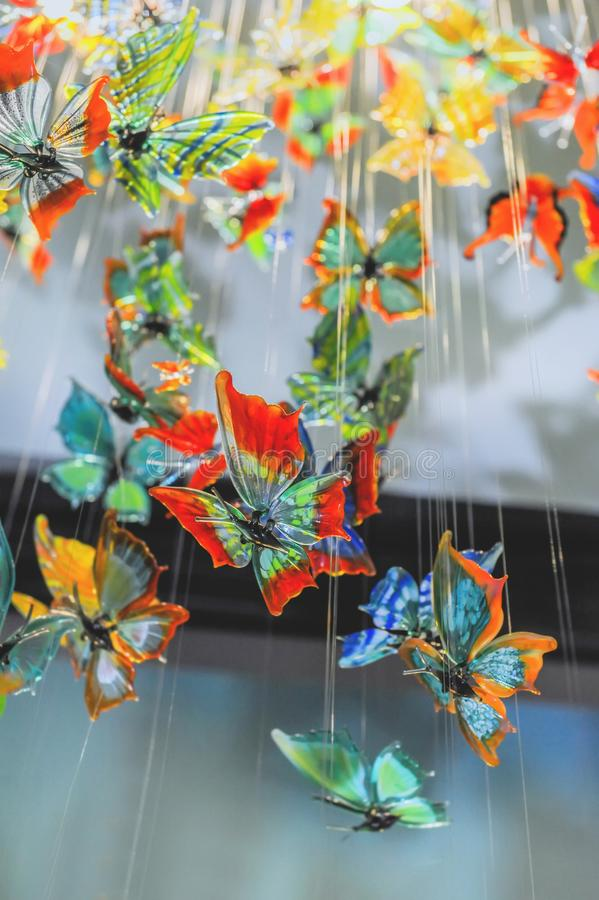 Glass colorful butterflies hang in the shop window royalty free stock photography