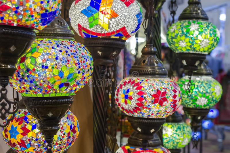 Glass, colorful, traditional, decorative Turkish lamps hang on the ceiling in the store. Colorful authentic and traditionally handmade lanterns, chandeliers or stock photo