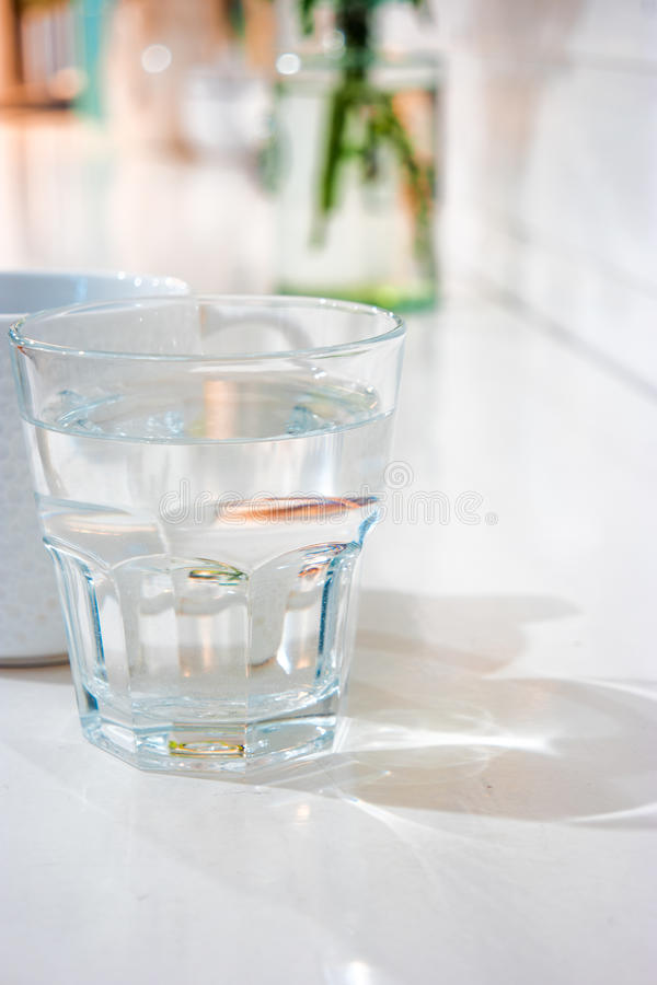 The glass of cool fresh wter on the table in. The glass of cool fresh wter on the white table in living room with a lot of space for text royalty free stock photos