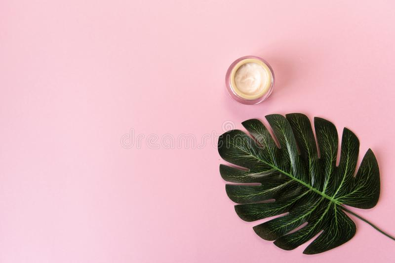 Glass cosmetic jar and tropical monstera leaf over pink background. Top view. Flat lay. Cosmetics, skin care, beauty, body royalty free stock image
