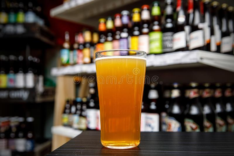 Glass of craft beer at the bar. Assortment of bottles on a blurred background. royalty free stock photos