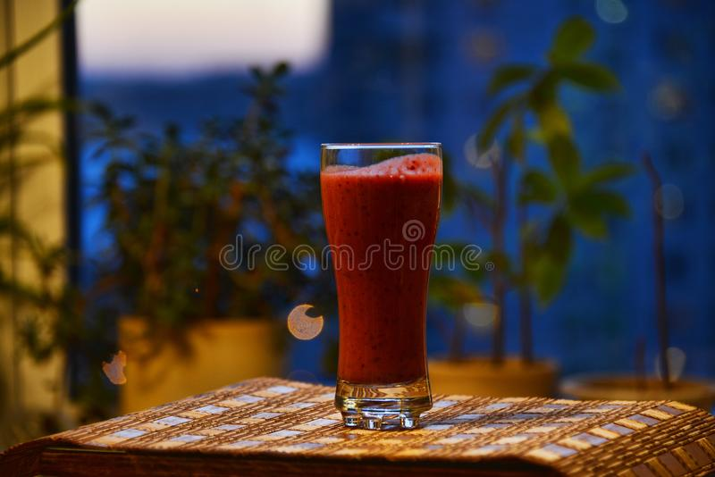 A glass with cranberry smoothies on a beautiful festive background stock image