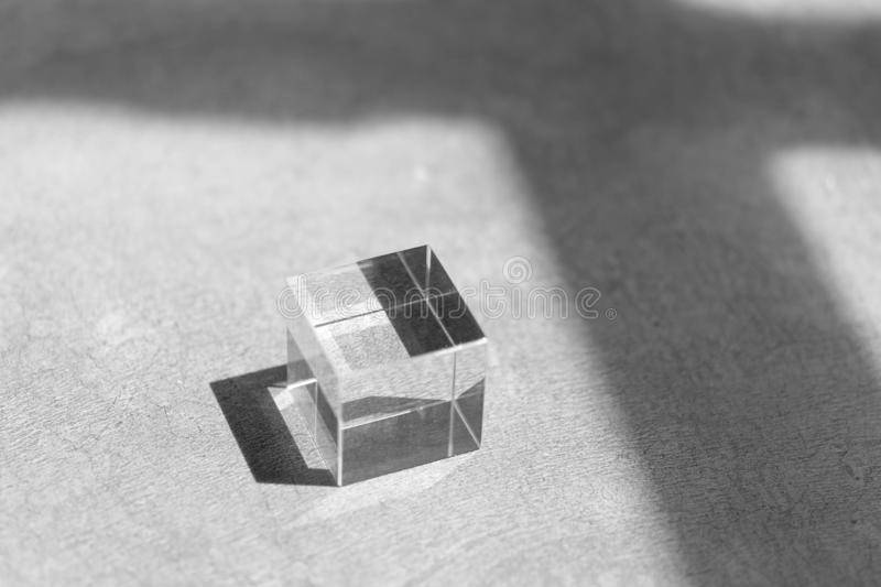 Glass cube on a floor with shadow in monochrome, stock illustration