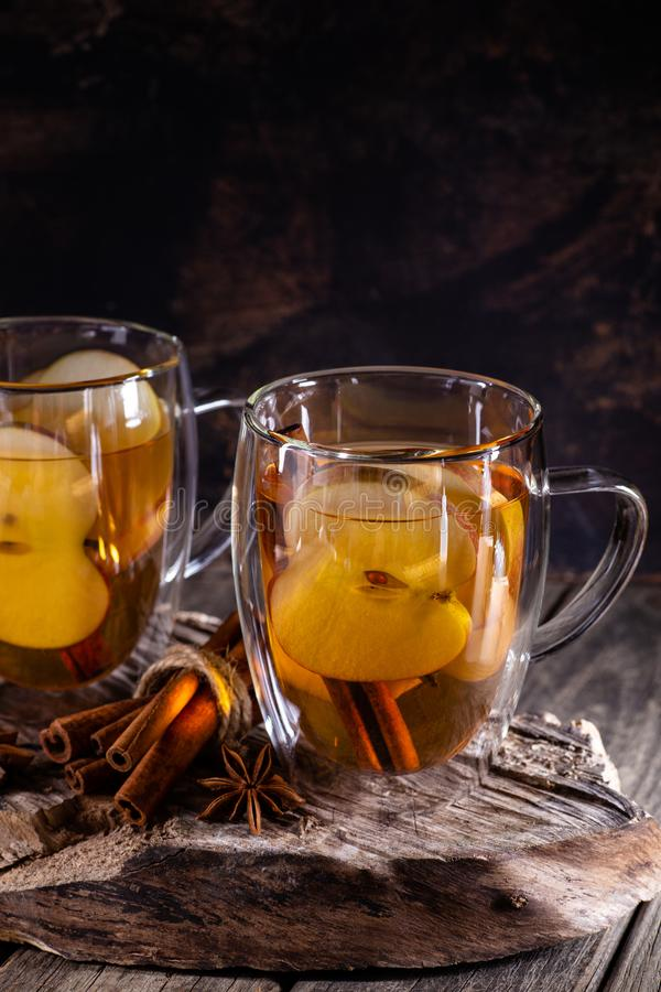 Glass Cup of Apple Cider. With sliced apples and cinnamon sticks on a rustic wooden surface and dark background with copy space stock photo