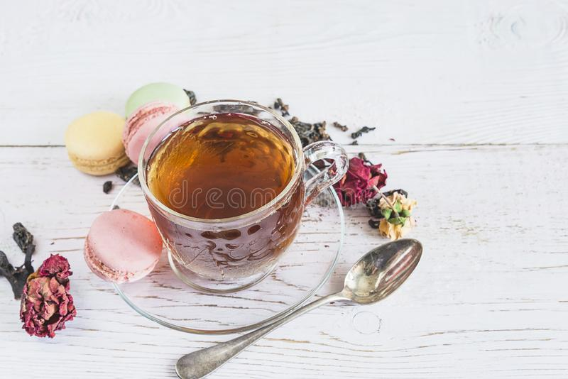 Tea time concept. Glass cup of black tea, french macaroons and dry rose buds on the rustic white paint wooden backgorund. Glass cup of black tea, french stock photo