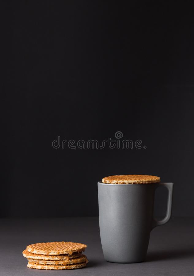 A glass cup of black tea with stack of dutch waffles on dark grey background. royalty free stock photography